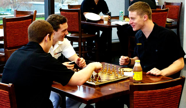 (From left) Midshipmen Sullivan, Huntsman and Demers take a break at the cafe inside Nimitz Library to play chess. (Photo by Rachel Boehm)
